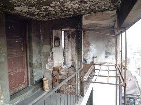 照片左边木门为完好无损的简易房,右边房东简易房大火的残壁,钢架地方是床,木框木门全部烧毁。(图:明慧网)