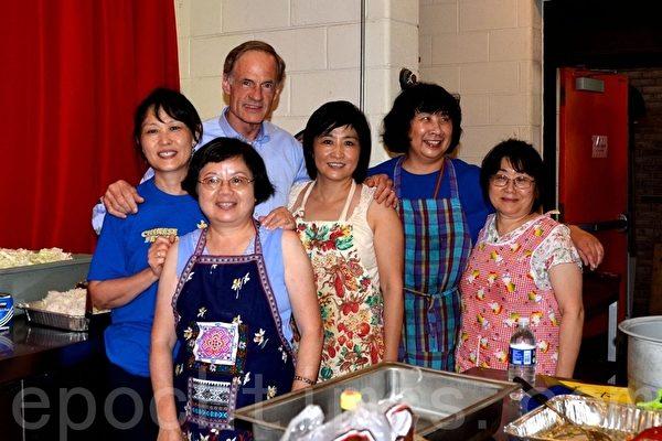 美国联邦参议员Tom Carper对中国节的美食情有独钟。图为他在厨房中与正在准备饭菜的部分志愿者合影。(摄影:良克霖/大纪元)