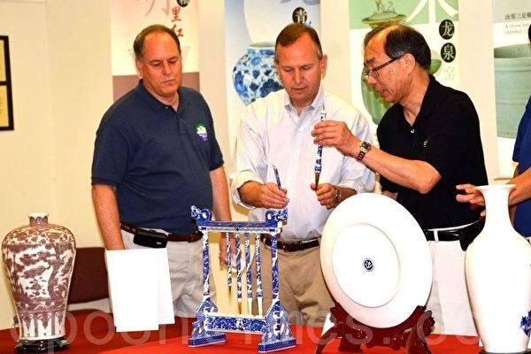 瓷器展负责人莫大镇先生(右一)正在向德拉华州州长Jack Markell(中)和纽卡索郡郡长Paul Clark介绍中国瓷器的悠久历史。(摄影:良克霖/大纪元)