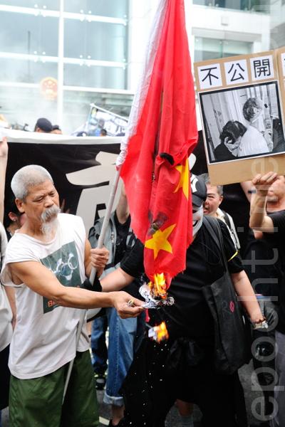 6月10日,2萬5港人就李旺陽事件抗議遊行當天,古思堯在中聯辦前燒黨旗。(攝影:宋祥龍/大紀元)