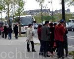巴黎埃菲尔铁塔下的退党服务中心真相信息台前,从旅游大巴下来的大陆游客在看真相展板。(大纪元)