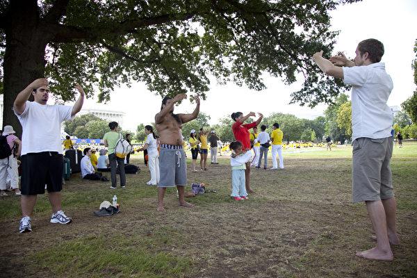 2012年7月12日,美国首都华盛顿,来自世界各地各族裔的部分法轮功学员,在美国国会山前集体炼功。民众当场学炼法轮功功法。(摄影:季媛/大纪元)