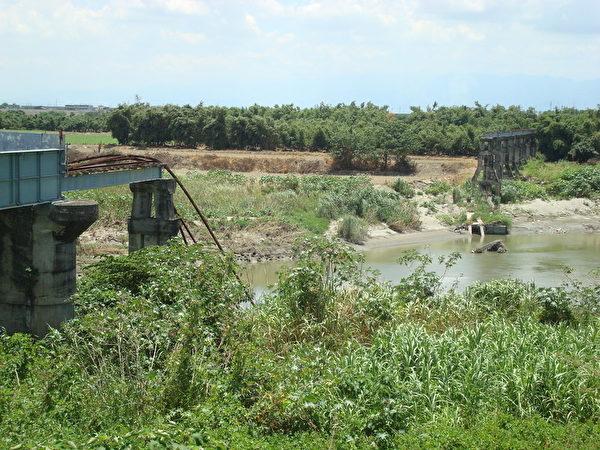 走過百年的雲林北港復興鐵橋,數座橋墩不堪溪水沖刷已沒入溪中。(攝影:黃麗醫/大紀元)
