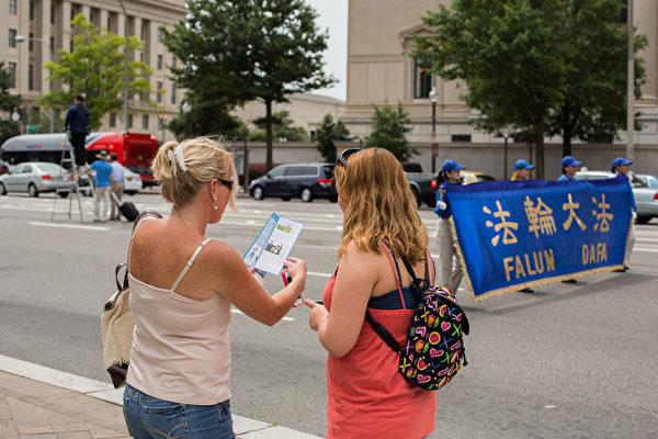 """2012年7月13日,法轮功学员在美国华盛顿DC举行""""解体中共、停止迫害大游行"""",民众正在阅读法轮功真相传单。 (摄影:陈虎/大纪元)"""