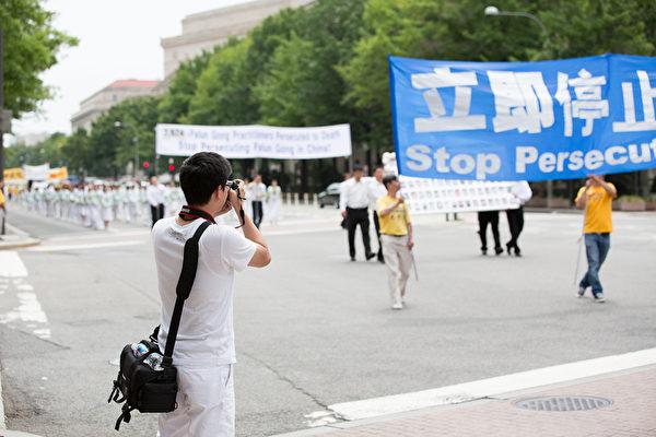 """2012年7月13日,法轮功学员在美国华盛顿DC举行""""解体中共、停止迫害大游行"""",民众举起拍照。 (摄影:陈虎/大纪元)"""