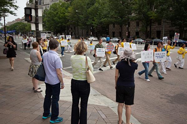 """2012年7月13日,法轮功学员在美国华盛顿DC举行""""解体中共、停止迫害大游行"""",路旁民众驻足观看。 (摄影:陈虎/大纪元)"""