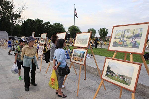 2012年7月13日,美国华盛顿DC,法轮功真相图片展的现场,民众正在看真相图片。(摄影:李明/大纪元)