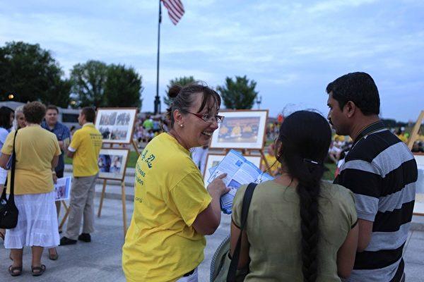 2012年7月13日,美国华盛顿DC,法轮功真相图片展的现场,民众正在听法轮功学员讲真相。(摄影:李明/大纪元)