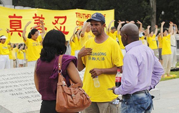 2012年7月13日,美国华盛顿DC,法轮功真相图片展的现场,民众正在听法轮功学员讲真相。(摄影:连震黎/大纪元)