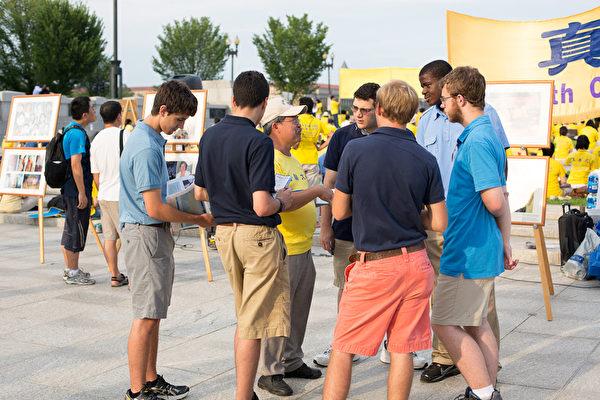 2012年7月13日,美国华盛顿DC,法轮功真相图片展的现场,民众正在听法轮功学员讲真相。(摄影:陈虎/大纪元)