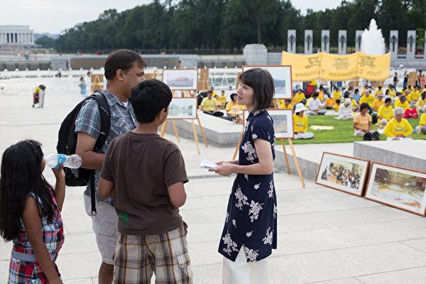 2012年7月13日,美国华盛顿DC,法轮功真相图片展的现场,民众正在听法轮功学员(右)讲真相。(摄影:陈虎/大纪元)