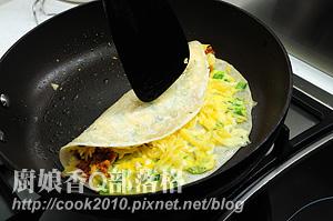 再用铲子将整个饼卷起(摄影: 新唐人电视台 提供)