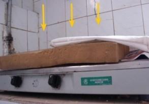 煤气灶已无法使用,平时铺着报纸编织袋接流下来的屎尿汤(这是清扫后拍摄的情形)(图片来源:明慧网)