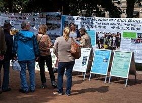 二零一二年七月十四日,芬兰法轮功学员在首都赫尔辛基的海滨公园举办讲真相活动,人们纷纷停下脚步了解真相。(图:明慧网)