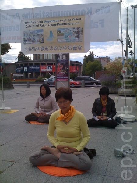 在国际器官移植会议开会地点前,法轮功学员在展示功法。(摄影:刘成/大纪元)