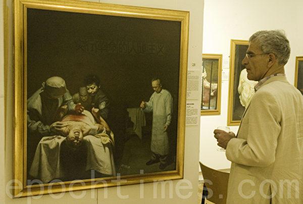 东格林斯蒂德镇退休工人麦克‧华莱士在真善忍国际美展作品《苏家屯的邪恶》前。(摄影:梁思成/大纪元)