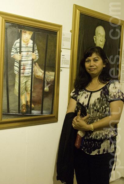 东格林斯蒂德镇当地艺术家协会的成员芮恩‧斯塔基在真善忍国际美展作品《为什么》前留影。(摄影:梁思成/大纪元)