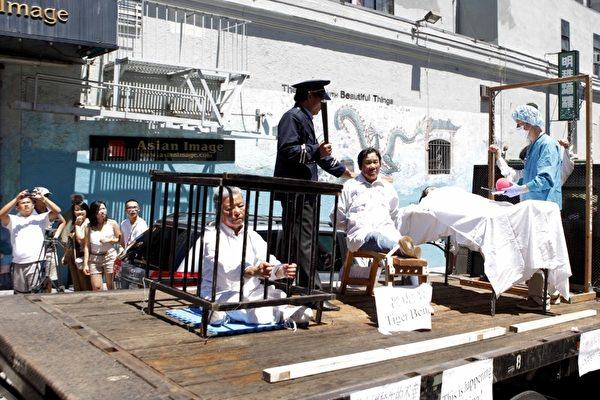 反迫害大游行队伍中,模拟酷刑车向人们展示了法轮功学员13年来在大陆所遭受的残酷迫害,吸引了路人关切的目光。(摄影:大纪元/李明)