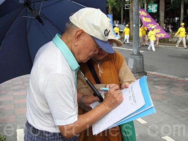 游行队伍行进时,围观的民众听闻台湾法轮功学员钟鼎邦,受到江西赣州国安局的非法抓捕,而加入征签,希望藉由征签尽一份力量。(摄影:罗郁棠/大纪元)