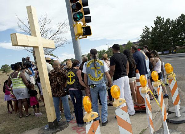 2012年7月20日,科羅拉多州奧羅拉,民眾聚集在案發劇院附近的十字路口哀悼死難者。(DON EMMERT/AFP PHOTO)