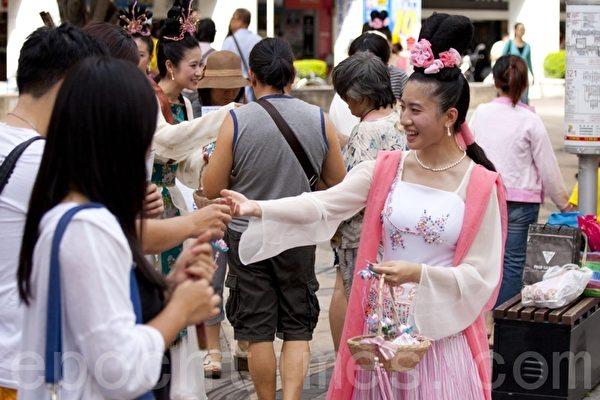 游行队伍还有法轮功女学员穿着仙女服饰,传递法轮大法的真相资料和小卡片,受到路人的喜爱。(摄影:吴柏桦/大纪元)