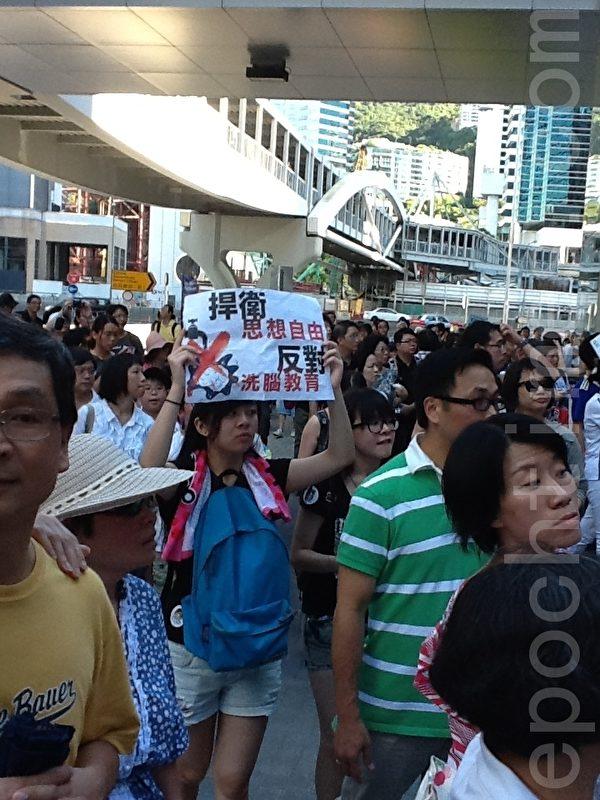 年青人高舉自製抗議標語牌(攝影:吳雪兒/大紀元)