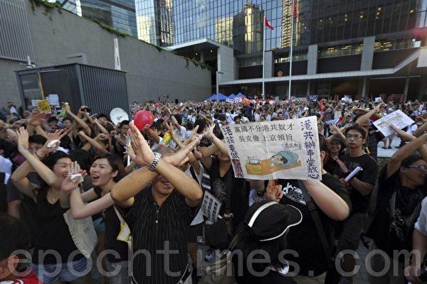 游行人士在政府总部外以手势表达不要洗脑国民教育。(摄影:潘在殊/大纪元)