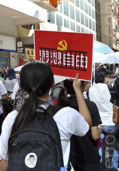 一名年青人高举自制抗议标语牌(摄影:潘在殊/大纪元)