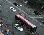 """7月21日,北京遭受罕见暴雨袭击,中共官方报死亡人数攀昇至77人,但公众对此普遍质疑。面对社会舆论压力,中共九常委集体""""失声"""",中宣部下令对媒体进行严控。北京暴雨被""""辗转腾挪""""后似乎在公众视线中消失,取而代之的是一场万里之外的奥运比赛。(ChinaFotoPress/Getty Images)"""