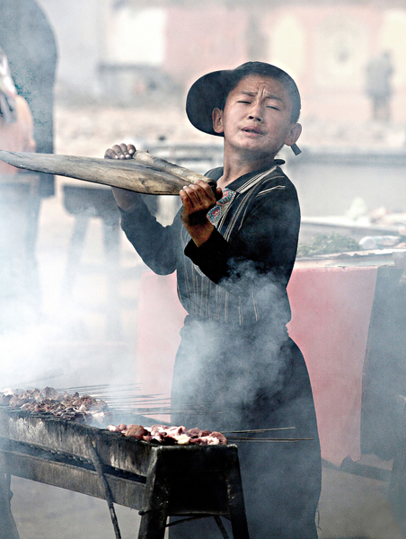 《生活压力下的少年》 :这幅作品表现了一个新疆未成年的孩子,在烟熏火燎下烧烤羊肉串叫卖,那个表情俨然是一个老卖主了,如果不是生活压力下,哪个父母会让自己的未成年的孩子担起如此艰辛的生活重担?画面气氛强烈,恰到好处的抢到人物的最佳动作和表情,明与暗,实与虚对比出主体与环境的层次。(伊罗逊评历届摄影大赛获奖作品)