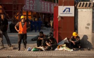 過去,中國許多基建工地工人要日日夜夜地工作,今天,許許多多工地處於停滯狀態,建築工人每天不過工作8個小時,甚至每週還有一天的休息。圖為2012年5月,北京市某工地工人在門口休息的場面。(Ed Jones/AFP/GettyImages)
