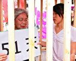 台湾公民钟鼎邦因探亲在中国遭逮捕,8月7日钟家与多个声援社团共上百人,上午到总统府前凯道抗议,现场也准备一个木制牢笼准备自囚。图为钟鼎邦的女儿钟爱(右)与钟鼎邦的妈妈(左)关进牢笼自囚。(摄影:林伯东/大纪元)