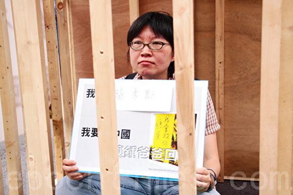 台湾公民钟鼎邦因探亲在中国遭逮捕,8月7日钟家与多个声援社团共上百人,上午到总统府前凯道抗议,现场也准备一个木制牢笼,钟家人与社团代表轮流自囚,随即并静坐。图为台湾人权促进会 秘书长 蔡季勋在牢笼中。(摄影:林伯东 / 大纪元)