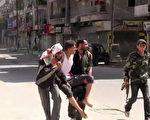叙利亚政府军和反抗军自7月20日,开始在阿勒颇是展开激战,双方企图抢下该国第一商业大城的控制权。图为8月5日在阿勒颇市战乱中,被反抗军搀扶救出的受伤民众。(JAMES FOLEY/AFP/GettyImages)