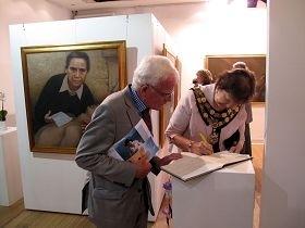 伦敦里士满市长丽塔•帕尔默女士认真欣赏真善忍美展作品后在留言簿上签名。(图:明慧网)