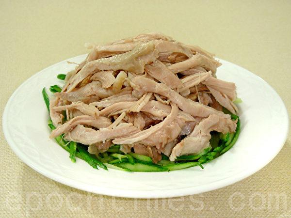 雞肉絲放在小黃瓜絲上,再淋上怪味汁,撒上蔥花即完成。(攝影:林秀霞 / 大紀元)