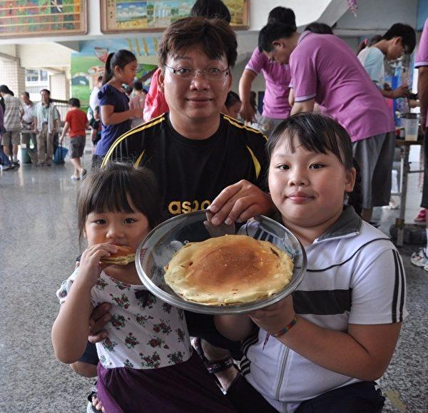 蔡雨洁、蔡旻真小朋友,在爸爸的协助下,完成了直径25公分的超大铜锣烧,任两姐妹开心不已!(高雄市社教馆提供)