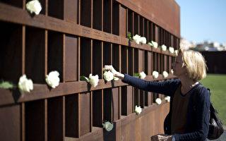 8月13日是开始建筑柏林墙的日子。一位妇女在柏林墙前献上白花(DAVID GANNON/AFP/GettyImages)