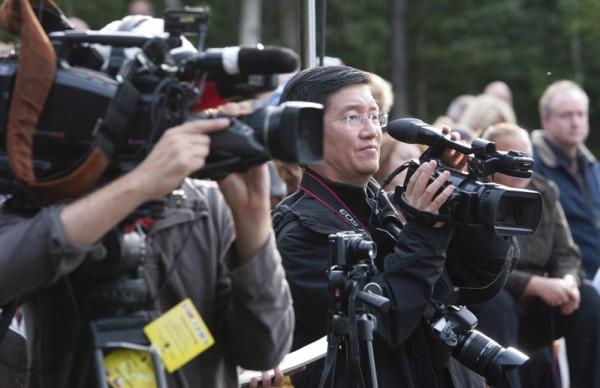 本周三,新华社渥太华分社社长张大成(中)在加拿大总理哈珀(Stephen Harper)到访加拿大西北特区石油钻井和勘探中心Norman Wells时,进行视频拍摄。(加通社)