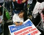 图为在呼吁全面改革美国移民法的游行中睡着的孩子(Photo by David McNew/Getty Images)