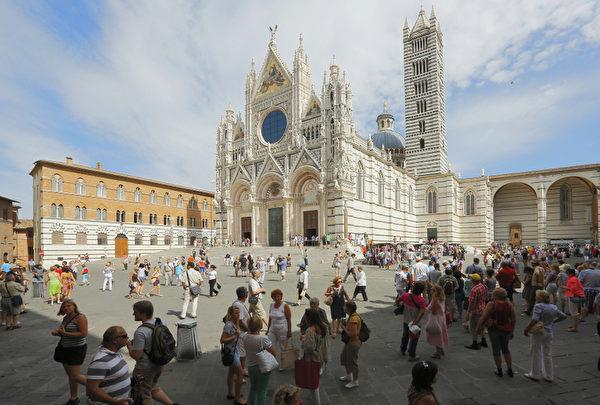 2012年8月30日,意大利锡耶纳大教堂前广场上的游客。(FABIO MUZZI / AFP)