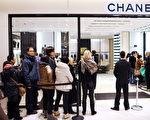 法国巴黎一间百货公司,民众排队准备入内购物。(MARTIN BUREAU/AFP)