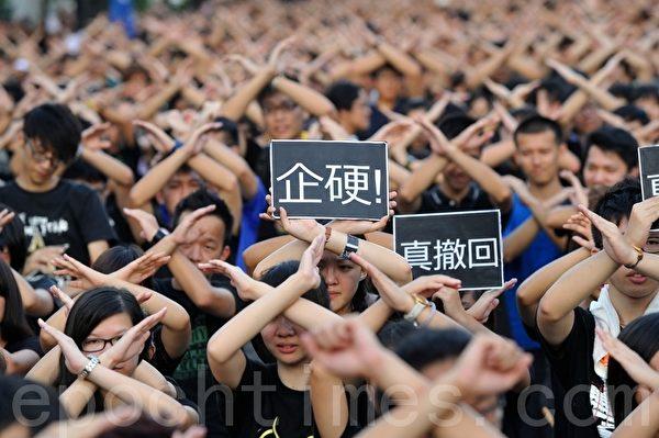 """8,000名大专生,在额前绑上黑丝带,又以双手做出交叉手势,批评政府是假让步,要求政府撤回科目,并齐声高喊:""""CY要撤科!""""(摄影:宋祥龙/大纪元)"""