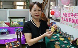 嘉義市西區衛生所護士洪金鶯11日舉辦個展,手持米粒形狀的「粒粒皆辛苦」石頭彩繪作品。(攝影:李擷瓔/大紀元)