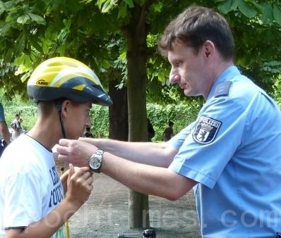 柏林一个小学的仲夏节上,警察帮学生戴上自行车头盔,调节好自行车高度,指导学生骑车时要遵守交通规则。警察还提供有关交通安全的宣传纸张和图画。 (摄影:吴茵/大纪元)