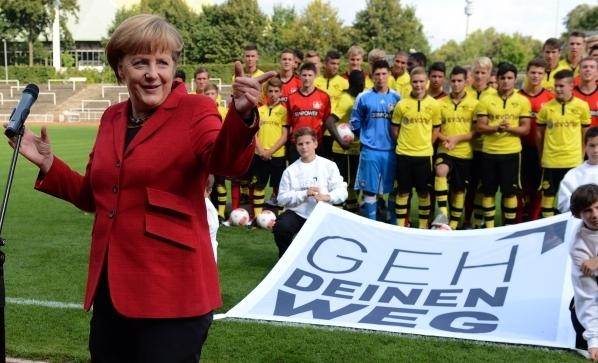 默克爾是個足球迷,她會為足球項目做宣傳。她呼籲在足球賽場上能有更多的「融合與包容」,德甲聯賽的參賽隊員手持寫有「走自己的路」(Geh deinen Weg)字樣的橫幅或T恤出場,以示對這一項目的支持。 (PATRIK STOLLARZ/Getty Images)