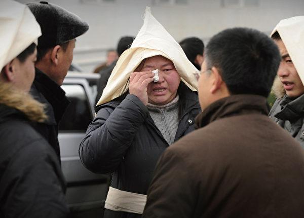 2009年11月21日,黑龍江鶴崗新興煤礦發生地底瓦斯突然噴發事故,造成近百人罹難,震動全中國。圖為一罹難家屬為罹難者舉行喪禮。(AFP)