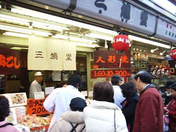 出名的人形烧店铺前,人们焦急地等待着即时制作的人形烧。(摄影:任子慧、赵莫迦 / 大纪元)