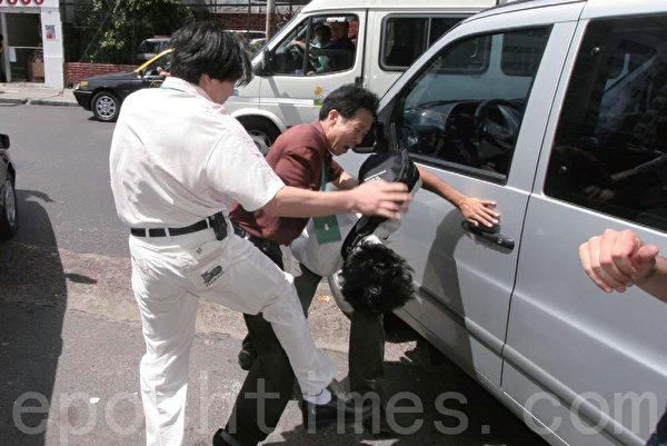 2005年12月14日,罗干到阿根廷期间,中共大使馆派出暴徒殴打抗议的法轮功学员。打手着红衣服、白衣服,脖子上挂有绿色牌子。 (摄影:Carlos Carbone/大纪元)