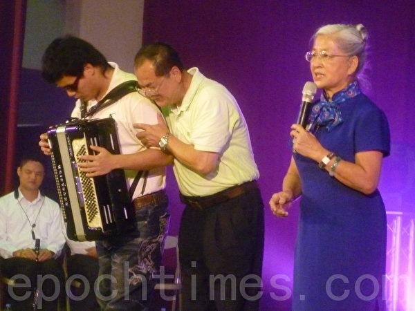 陳素嬰老師(右)介紹手風琴多重障礙表演者廖庭澔(左)及他的父親。(攝影:詹亦菱/大紀元)